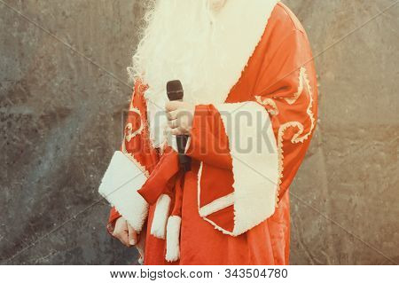 The actor dressed as Santa Claus performs on stage with a microphone against a black background. Close up. stock photo