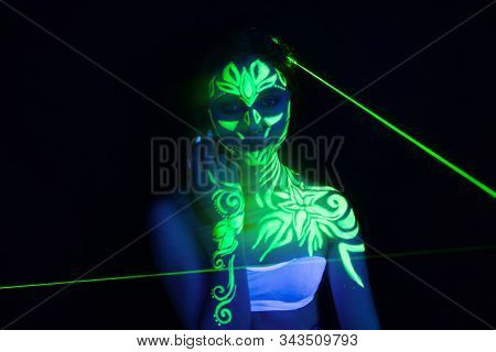 Body art on the body and hand of a girl glowing in the ultraviolet light. Body art glowing in ultraviolet light stock photo