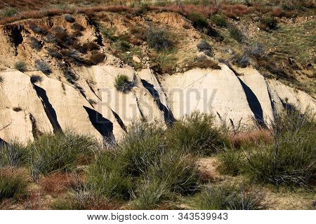 Arid grassy plain including chaparral shrubs with sandstone rock bluffs beyond taken at the Mojave Desert in Cajon, CA stock photo