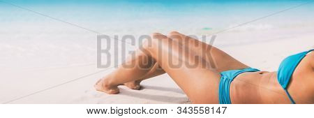 Summer beach bikini body woman lying on white sand sun tanning smooth legs sun tan for laser hair removal concept banner panoramic background. stock photo