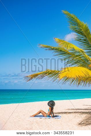 Caribbean beach tourist relaxing in Barbados, cruise shore day. Woman sunbathing sun tanning under palm tree on sand on Dover beach, famous resort tourist tropical destination. stock photo
