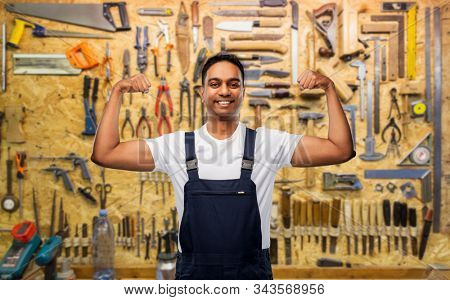 profession, construction and building concept - happy smiling indian worker or builder showing his power over work tools on background stock photo