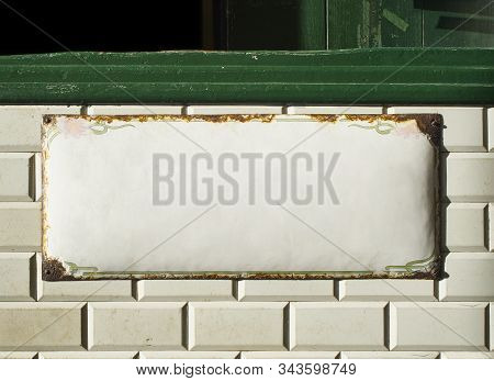 Blank metallic plate on an antique wall tiled with Metro tiles background. stock photo