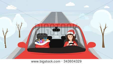 Girl in santa claus hat driving car. Woman in Christmas costume sitting at front seat of automobile with big bag with presents. Female driver character in festive X-mas clothing, winter snowy road stock photo