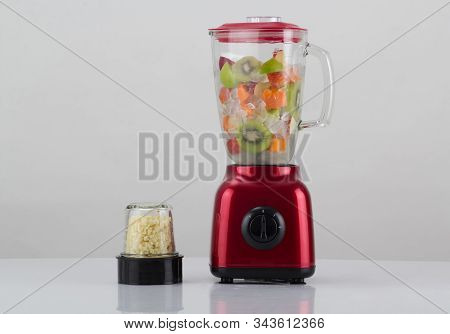 Red blender with fruits inside and the garlic chopper isolated on white background stock photo