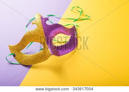 Mardi gras mask and beads. A festive, colorful group of mardi gras or carnivale mask on a purple background. Venetian masks. stock photo