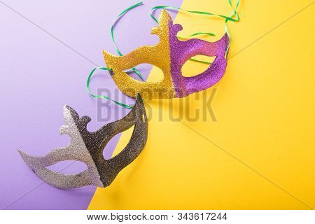 A festive, colorful group of mardi gras or carnivale mask on a purple background. Venetian masks.Gold purple and green glittery mardi gras mask on a white background stock photo