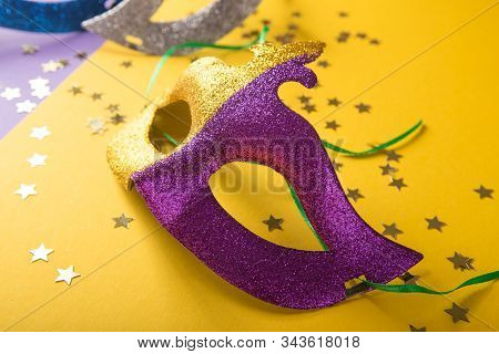 Mardi gras mask and beads. A festive, colorful group of mardi gras or carnivale mask on a yellow purple background. Venetian masks. stock photo