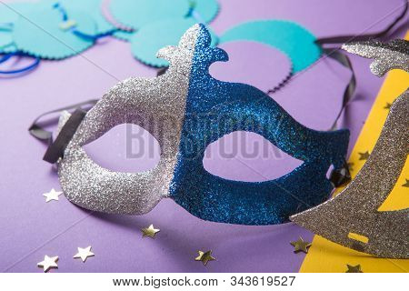 A festive, colorful group of mardi gras or carnivale mask on a yellow purple background. Venetian masks. Colombina face cover for masquerade or costume party. Man and woman ball masque for theater or opera, mardi gras festival or brazil parade. Fashion an stock photo