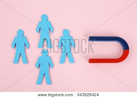 Magnet attracting paper people on pink background, flat lay stock photo