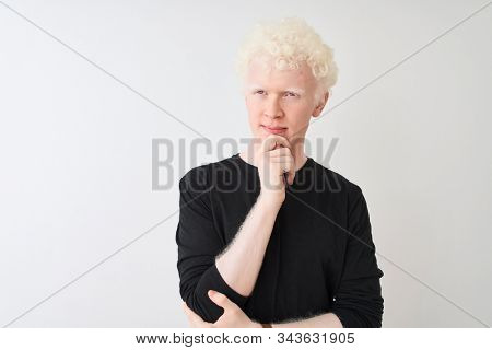 Young albino blond man wearing black t-shirt standing over isolated white background with hand on chin thinking about question, pensive expression. Smiling with thoughtful face. Doubt concept. stock photo