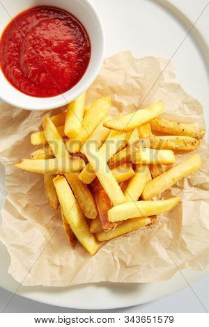 Fries or french fries on white restaurant plate with tomato sauce isolated. Sweet potato finger chips, golden french-fried potatoes or junk food snack on kraft paper closeup stock photo