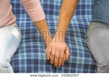 A man holds a woman's hand while sitting on a sofa. Man's hand hold by a woman hand. Friendship and love concept between man and woman. Photo of a couple holding hands. stock photo