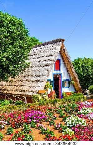 Beautiful traditional house in Santana, Madeira, Portugal. Wooden, triangular houses represent a part of Portuguese heritage. Front garden with beautiful colorful flowers. Tourist attraction stock photo