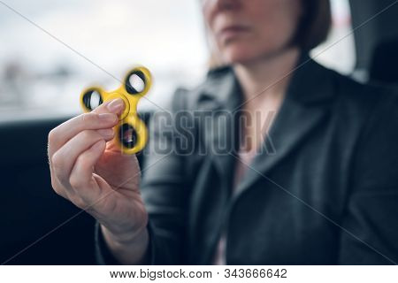 Businesswoman playing with fidget spinner in car while sitting at the backseat of the vehicle and commuting to work, selective focus stock photo