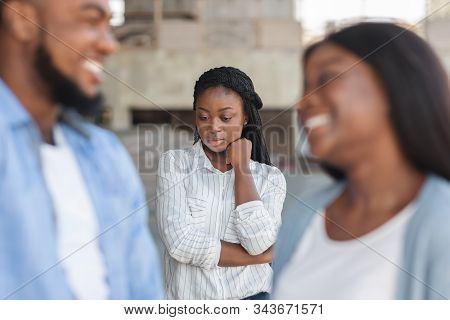 Third wheel. Upset black girl jealous to her dating friends, standing alone on background outdoors, selective focus stock photo