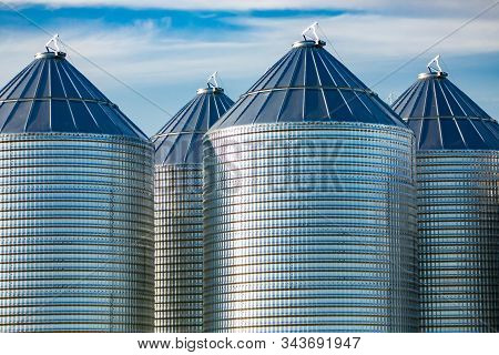 Modern and clean bulk grain storage silos are seen on a large farm in Alberta, Canada. Stockpile of grain, cereal, wheat, maize, rice in metal towers stock photo