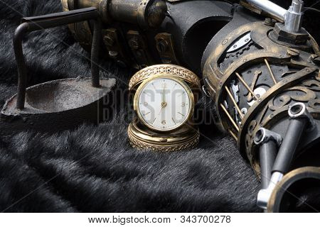 Old gold clock with antique fire iron and steampunk mechanical arm stock photo