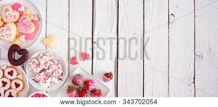 Valentines Day banner with corner border of assorted sweets and cookies. Above view over a white wood background. Love and hearts theme. Copy space. stock photo