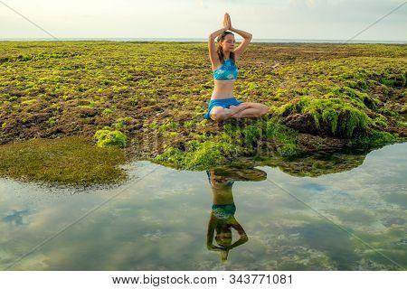 Young woman, meditating, practicing yoga and pranayama at the beach. Sunrise yoga practice. Hands raising in namaste mudra. Water reflection. Yoga retreat. Melasti beach, Bali, Indonesia stock photo