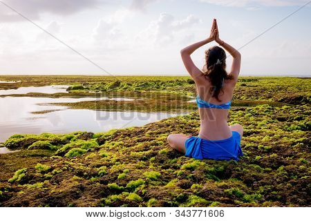 Young woman, meditating, practicing yoga and pranayama at the beach. Sunrise yoga practice. Hands raising in namaste mudra. View from back. Copy space. Melasti beach, Bali, Indonesia stock photo