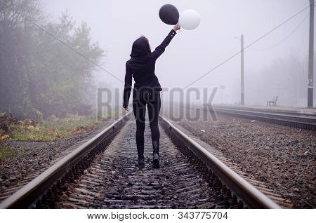 Lonely girl in black clothing stands back between the rails in a fog. She holds a black and white balloon in her hand and loking at it. Concept of choice, good and evil, way of life stock photo