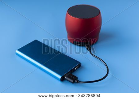 Power bank for charging mobile devices and devices. Blue smartphone charger with power bank. External battery for wireless headphones and speakers on a blue background. stock photo