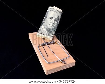 Dollars in a mousetrap on a black background. Wooden trap with bait and mechanism for rats and mice. Concept: happiness is not money, addiction stock photo