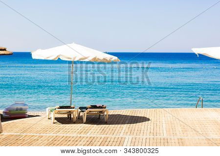 summer time resort hotel beach coast line scenic landscape view of umbrella lounge furniture deck chair on wooden deck floor and Red sea blue water horizon background stock photo