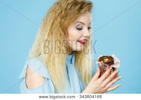 Sweet food sugar make us happy. Attractive blonde woman holds yummy chocolate cupcake in hand, craving for cake. Appetite and tasty meal dessert. stock photo