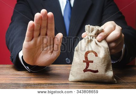 Businessman refuses to give pound sterling GBP money bag. Refusal to grant loan mortgage, bad credit history. Refuses cooperate. Financial difficulties. Economic sanctions, confiscation funds stock photo