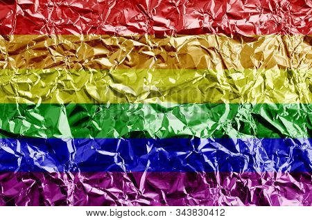 LGBT community flag depicted in paint colors on shiny crumpled aluminium foil closeup. Textured banner on rough background stock photo
