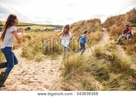 Three Children Having Fun Exploring In Sand Dunes On Winter Beach Vacation Run To Father stock photo