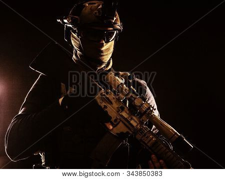 Army marksman with sniper rifle in darkness stock photo