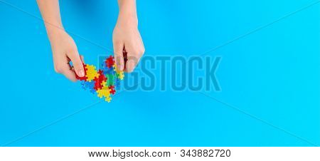 Child hand holding colorful heart on light blue background. World autism awareness day concept stock photo