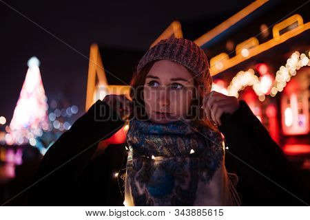 Portrait - Young attractive redhead girl hanging out in amusement theme park with bright vivid colorful attractions and installations background - Eastern European winter without snow in Latvia Riga stock photo
