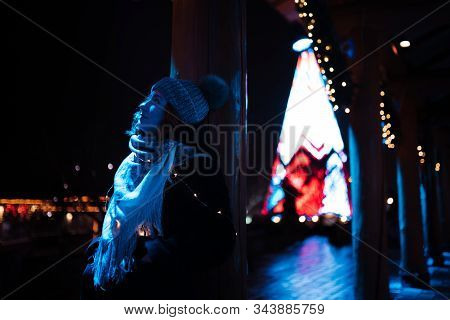 Young attractive redhead girl hanging out in amusement theme park with bright vivid colorful attractions and installations background - Eastern European winter without snow in Latvia Riga stock photo