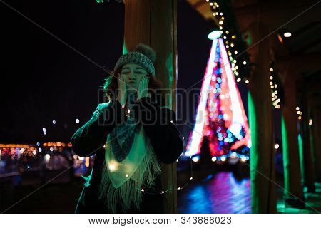 Making faces - Young attractive redhead girl hanging out in amusement theme park with bright vivid colorful attractions and installations background stock photo