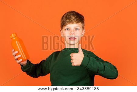 You will like this product. Small boy show thumbs up for juice orange background. Vitamin drink. Drinking product. Bottle with organic product. Healthy drinking habits. Promoting product stock photo