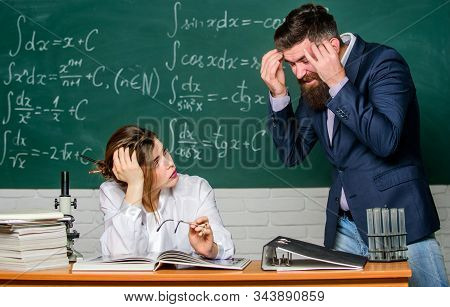 Problem solving. Bearded man and sexy woman consider problem at lesson. Problem at school. Educational problem. Finding solution. Communication skills stock photo