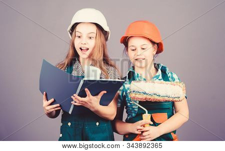 Kids girls planning renovation. Children sisters run renovation their room. Amateur renovation. Sisters renovating home. Home improvement activities. Kids choosing paint colour for their new room stock photo