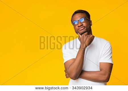 Thought. Pensive Black Guy Thinking Touching Chin Standing On Yellow Background. Studio Shot, Copy Space stock photo