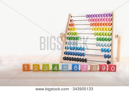 Bright colored wooden bricks with numbers and abacus toy with copy space, Numeral cubes with numbers 1, 2, 3, 4, 5, 6, 7, 8, 9 and 0 & colorful abacus, Child development, early math skills concept stock photo