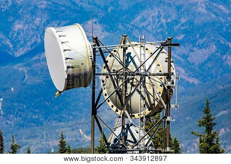 A close up and detailed shot on the top of a cellular network base station, two circular microwave antennas are housed to a steel lattice tower stock photo