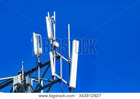 A close up and detailed view of electronic communication equipment atop a cell site tower, multiple white antenna and RRH, Remote Radio Head, with copy space stock photo