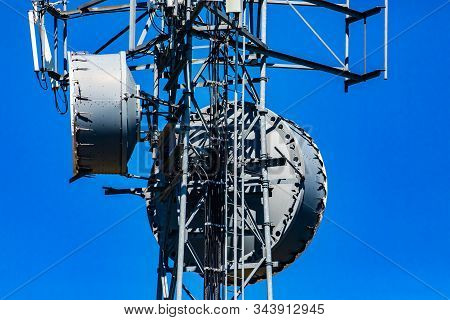 A closeup and detailed view of a cellular network base station with microwave antenna fixed to metal pylon, cause of electromagnetic pollution stock photo