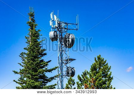 A cellular base station, or cell site tower, is seen between green trees and a blue sky. Electronic communications equipment on steel lattice tower stock photo