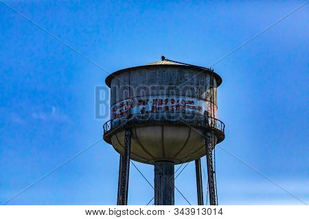 Architectural details of an old water storage tank tower. Weathered in a state of disrepair, covered in graffiti. Against a blue sky with copy space stock photo