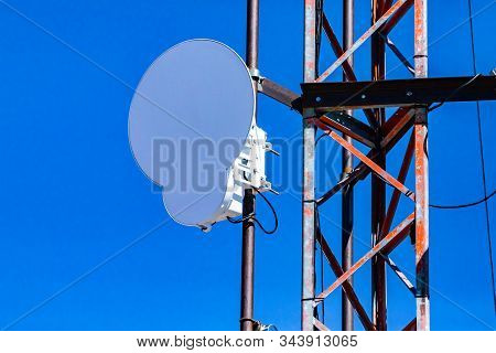 Closeup and detailed view of a circle microwave antenna fixed to steel lattice pylon. Emitting electromagnetic radiation linked to many health hazards stock photo