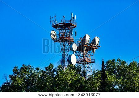 A low angle view of a cell site tower housed on a cable stayed steel lattice pylon, microwave antenna for 3G, 4G, 5G data transfer and signal boost stock photo